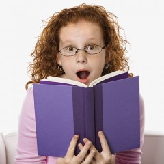 Caucasian female child sitting reading book looking surprised.